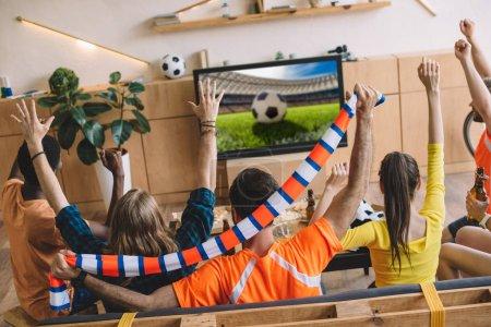 Photo pour Fans de football jeunes célébrer et faire oui gestes tout en étant assis sur le canapé au cours de la veille du football correspondent à la maison - image libre de droit