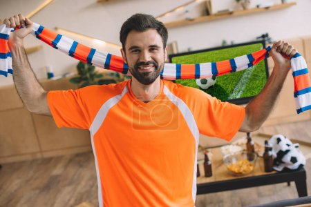 portrait of young man in orange fan t-shirt holding striped scarf and celebrating victory in soccer match at home