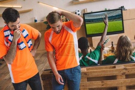 Photo pour Deux bouleversé les fans de football masculin en t-shirts orange et leurs amis en vert t-shirts gesticulant et célébrant la victoire au cours de la veille du football match à la maison - image libre de droit