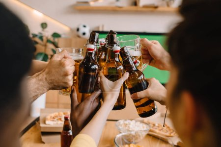 Photo for Partial view of soccer fans celebrating and clinking beer bottles and glasses over table with pizza, popcorn and chips at home - Royalty Free Image