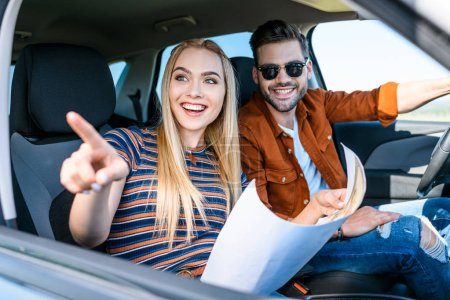 young woman with map in hand pointing by finger to smiling boyfriend sitting behind car wheel