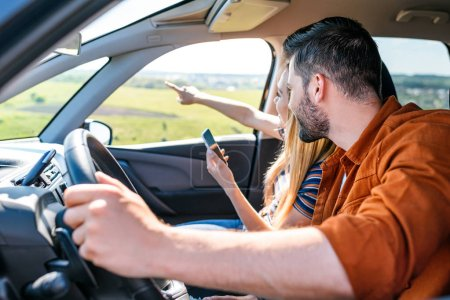 woman with smartphone in hand pointing by finger to boyfriend sitting behind car wheel