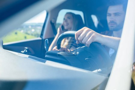 man driving car while his smiling girlfriend talking on smartphone