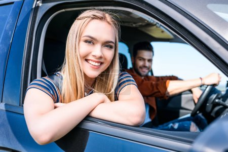 portrait of attractive smiling woman sitting in car with boyfriend