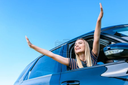 low angle view of young woman with wide arms leaning out from car window against blue sky