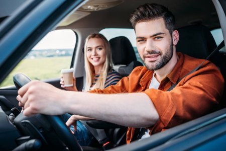 Photo for Portrait of young man sitting behind car wheel and his girlfriend with paper cup of coffee - Royalty Free Image