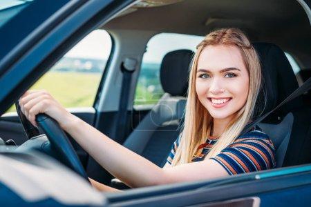 close up shot of smiling young woman sitting behind car wheel