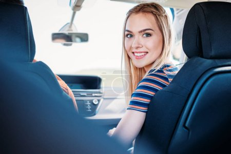 young smiling woman looking at camera while her boyfriend driving car