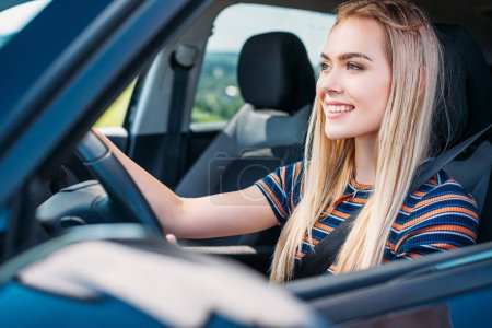 close up shot of smiling young woman driving car