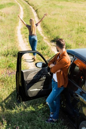 man with crossed hands standing near car and looking at girlfriend with wide arms in rural field