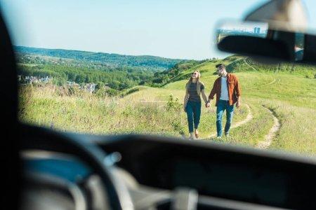vue lointaine du jeune couple main dans la main et marcher dans le domaine rural