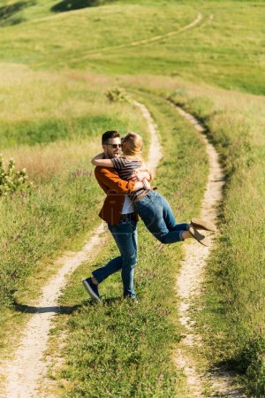 high angle view of young man spinning around girlfriend in rural field