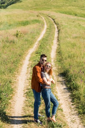 Photo for High angle view of happy stylish couple in sunglasses standing on rural meadow - Royalty Free Image