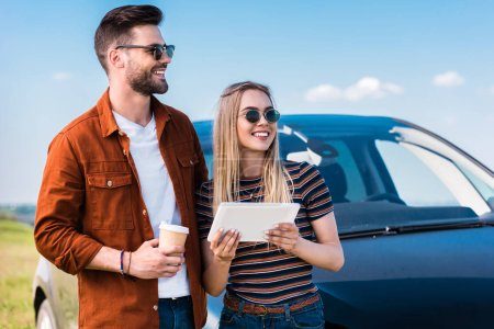 stylish couple in sunglasses standing with coffee cup and digital tablet near car