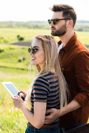 young stylish couple in sunglasses standing with digital tablet