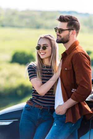 happy stylish couple in sunglasses standing near car