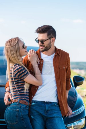 Photo for Smiling stylish couple in sunglasses standing near car - Royalty Free Image