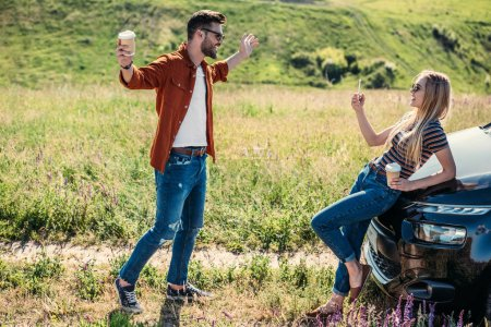 side view of woman taking picture of boyfriend with wide arms holding coffee cup near on rural meadow