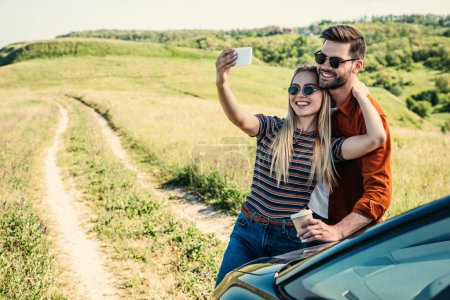 Photo for Smiling stylish couple in sunglasses with coffee cup taking selfie on smartphone near car on rural meadow - Royalty Free Image