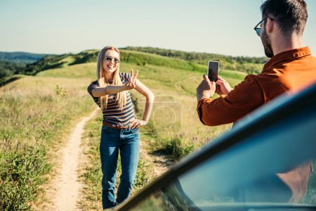 man taking picture of girlfriend doing peace sign near car on rural meadow