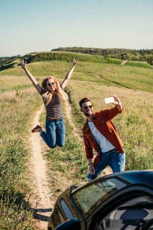smiling young woman jumping with wide arms while her boyfriend taking selfie on smartphone near car on rural meadow