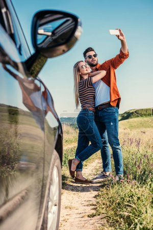 stylish man in sunglasses taking selfie on smartphone with smiling girlfriend near car on rural meadow