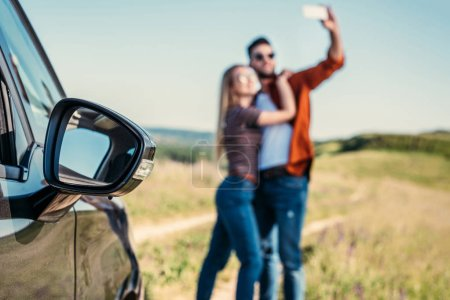 Photo for Close up view of side mirror of car and couple taking selfie on blurred background - Royalty Free Image