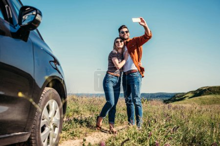 Photo for Stylish man taking selfie with girlfriend near car on rural meadow - Royalty Free Image