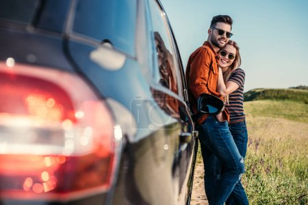 Photo for Happy stylish couple in sunglasses standing near car on rural meadow - Royalty Free Image
