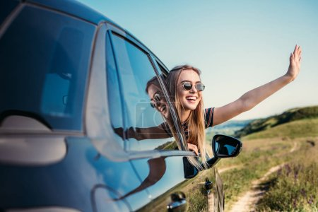 stylish woman in sunglasses leaning out from car window and waving hand on rural meadow