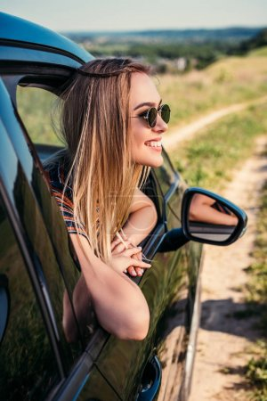side view of stylish woman in sunglasses leaning out from car window on rural meadow