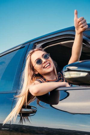 smiling stylish woman in sunglasses leaning out from car window and doing thumb up gesture