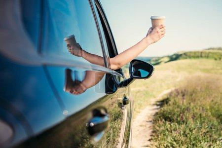 Photo pour Plan recadré de la femme penché la main avec une tasse de papier de café de la fenêtre de la voiture dans le champ rural - image libre de droit