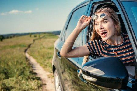 Photo pour Heureuse femme surprise penché par la fenêtre de la voiture - image libre de droit
