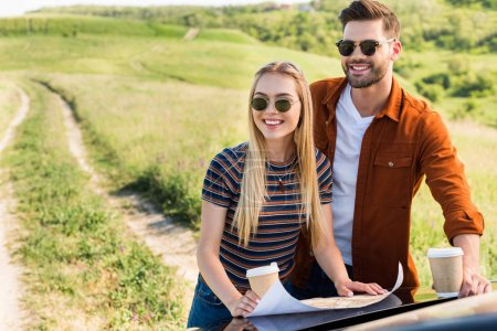 smiling stylish couple of travelers with paper cups of coffee looking for destination on map near car in rural field