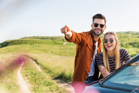 young stylish man pointing by hand to smiling woman near car on rural meadow