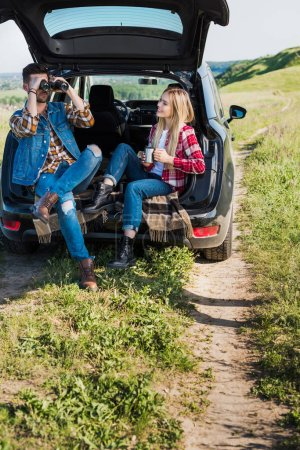 stylish male tourist looking through binoculars while his smiling girlfriend sitting near with coffee cup on car trunk in field
