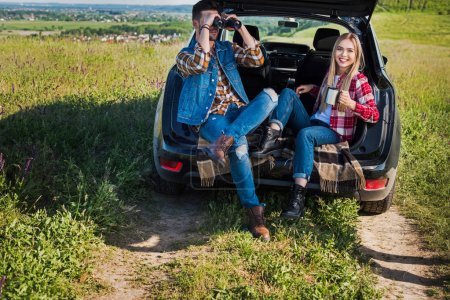 male tourist looking through binoculars while his smiling girlfriend sitting near with coffee cup on car trunk in rural field