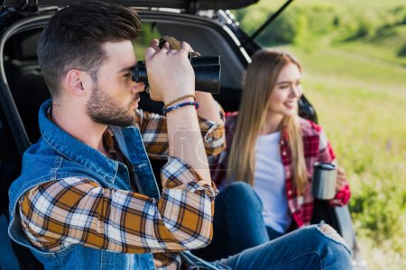 side view of male tourist looking through binoculars while his smiling girlfriend sitting near with coffee cup on car trunk