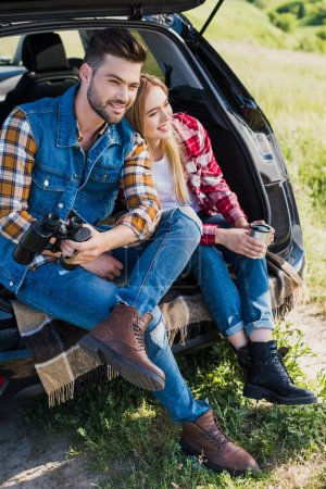 male tourist with binoculars and his smiling girlfriend sitting near with coffee cup on car trunk in field