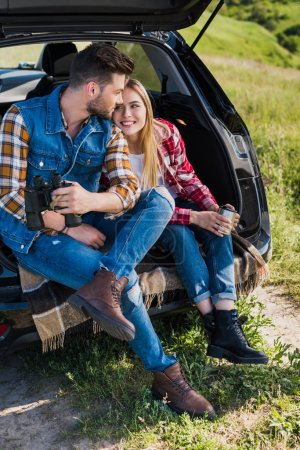 stylish male traveler with binoculars and his smiling girlfriend sitting near with coffee cup on car trunk in field