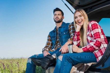 Photo for Smiling woman with coffee cup and her boyfriend sitting near on car trunk in field - Royalty Free Image
