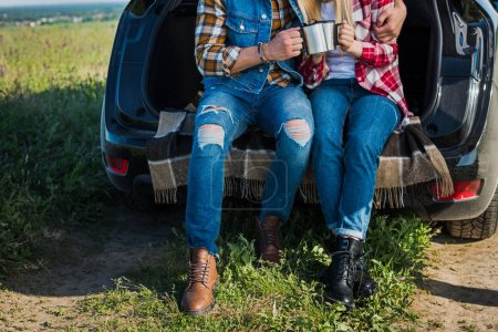 Photo for Cropped shot of couple of tourists clinking by coffee cups and sitting on car trunk in rural field - Royalty Free Image