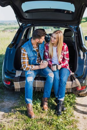 couple of stylish tourists with coffee cups sitting on car trunk in rural field