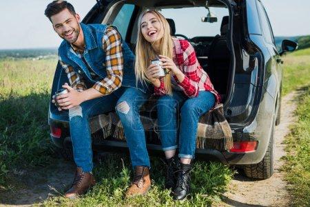 Photo pour Couple souriant de touristes élégants avec tasses à café assis sur le coffre de la voiture dans le domaine rural - image libre de droit