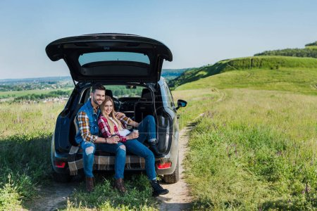 happy couple of stylish tourists with coffee cups sitting on car trunk in rural field