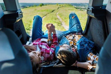 Photo pour Vue surélevée de couple de touristes posant sur le coffre de la voiture et se tenant la main dans le domaine rural - image libre de droit