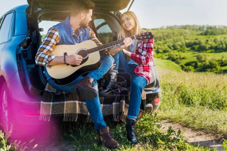 Photo for Young male traveler playing on acoustic guitar to smiling girlfriend on car trunk in rural field - Royalty Free Image