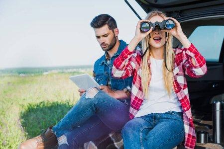 female tourist looking through binoculars while her boyfriend using digital tablet on car trunk in rural field
