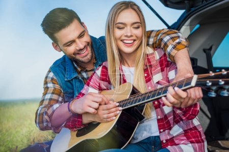 young man teaching smiling girlfriend to play on acoustic guitar while they sitting on car trunk